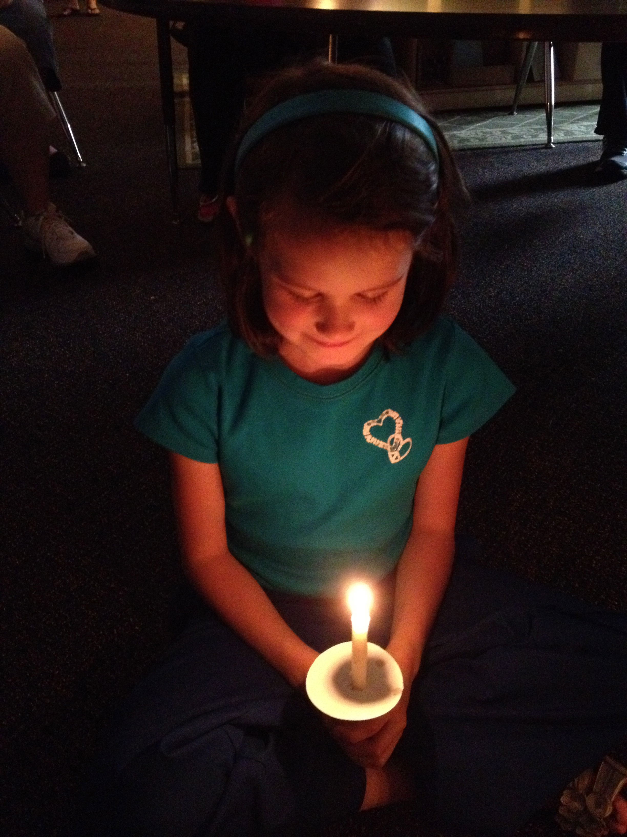 Child in contemplation with candle